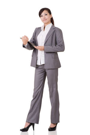 medium length: Asian business woman holding pad, full length portrait on white background. Stock Photo