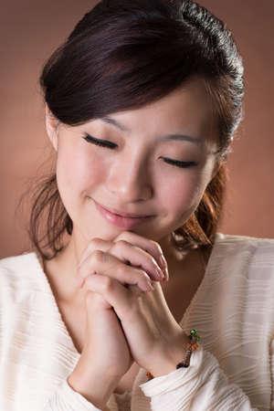 mujer orando: Mujer asiática que ruega, retrato de cerca el estudio de fondo marrón.
