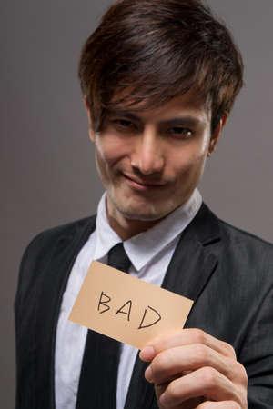 bad leadership: Asian business man holding card writing BAD.