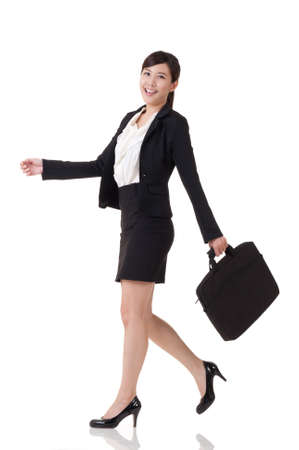 east asian: Asian business woman walking, full length portrait with reflection on studio white background. Stock Photo
