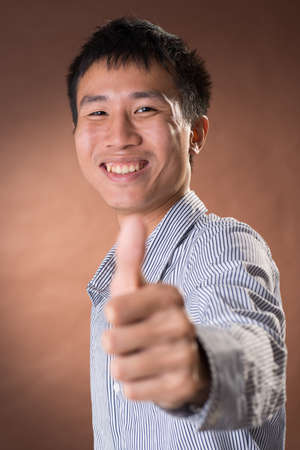 guileless: Young Chinese frank businessman give you an excellent gesture, closeup portrait in studio. Stock Photo