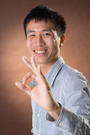 frank: Young Chinese frank businessman give you an Okay gesture, closeup portrait in studio.