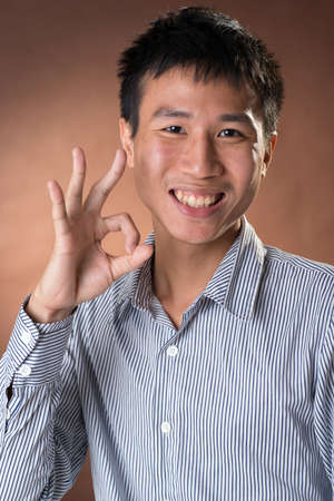guileless: Young Chinese frank businessman give you an Okay gesture, closeup portrait in studio.