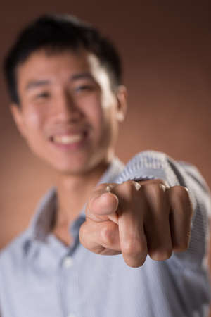guileless: Young Chinese frank businessman point at you, focus on finger, closeup portrait in studio. Stock Photo
