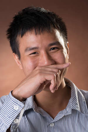 guileless: Young Chinese frank businessman with shy expression, closeup portrait in studio.