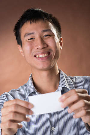 guileless: Young Chinese frank businessman holding blank white business card, closeup portrait in studio. Stock Photo