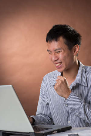 guileless: Exciting business man of Chinese sitting on chair and looking at laptop on desk in studio.