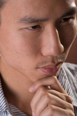 frank: Young Chinese frank businessman thinking, closeup portrait in studio. Stock Photo