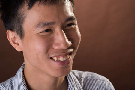 guileless: Young Chinese frank businessman smiling, closeup portrait in studio.