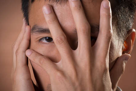 eye protectors: Young Chinese frank businessman cover his face by hand and peeking through finger, close up portrait in studio. Stock Photo