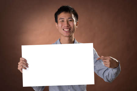guileless: Young business guy of Chinese holding blank board in studio.