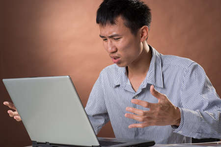 guileless: Angry business man of Chinese sitting on chair and looking at laptop on desk in studio.