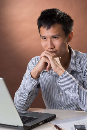 guileless: Successful business man of Chinese sitting, closeup portrait in studio.