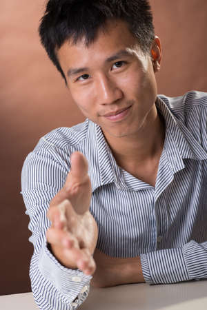 guileless: Successful business man of Chinese sitting and want to shake hand with you, closeup portrait in studio.