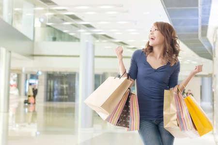 Cheerful shopping woman of Asian holding bags. 版權商用圖片