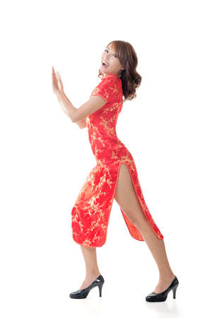 qipao: Chinese woman dress traditional cheongsam and push something at New Year, full length portrait isolated.