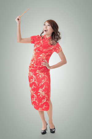 chop stick: Smiling Chinese woman dress traditional cheongsam standing and holding chopsticks at New Year, full length portrait  isolated.