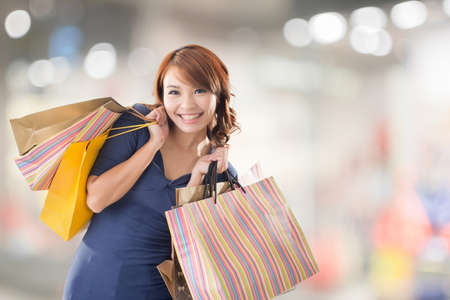 excitation: Cheerful shopping woman of Asian holding bags. Stock Photo