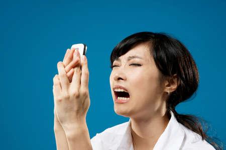 secretary phone: Yelling, closeup portrait of Asian business woman on studio blue background.