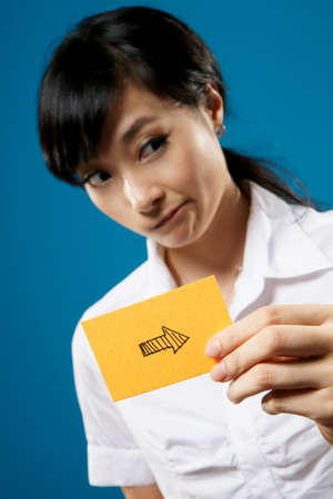 to designate: Right arrow on business card holding by Asian businesswoman on studio blue background.