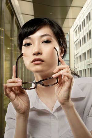 chinese sex: Attractive business woman of Asian holding glasses and standing in outside of office in Taipei, Taiwan, Asia.