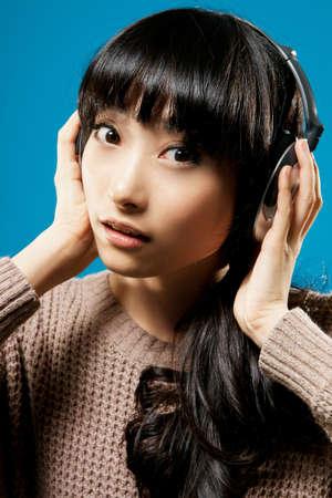 Asian girl listen music on studio blue background. photo