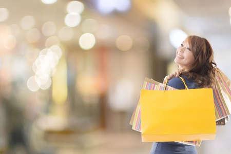 Cheerful shopping woman of Asian holding bags. Foto de archivo
