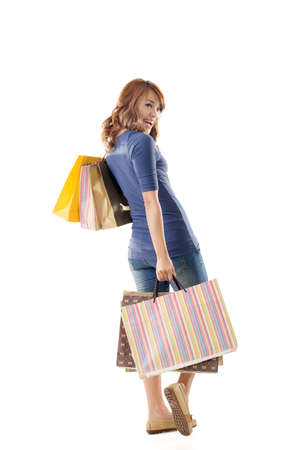 Cheerful shopping woman of Asian holding bags, full length portrait isolated. Imagens