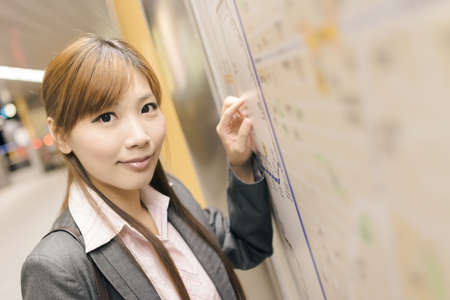 Asian young business woman look at you in front of the station map in the MRT station, shot at Xinyi business district, Taipei, Taiwan. Stock Photo