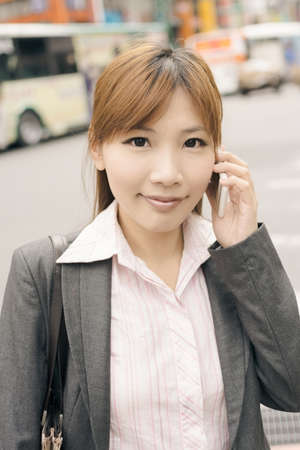 street shot: Asian young business woman use cellphone at the street, shot at Xinyi business district, Taipei, Taiwan. Stock Photo
