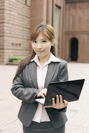street shot: Attractive Asian business woman use laptop in outdoor street, shot at Xinyi business district, Taipei, Taiwan.
