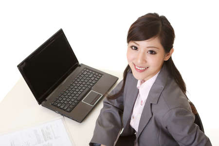 secretary desk: Attractive business woman sitting and smiling at you, closeup portrait. Stock Photo