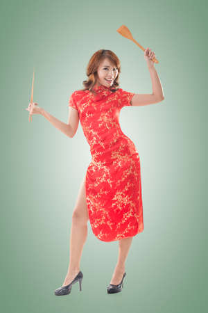 qipao: Smiling Chinese woman dress traditional cheongsam standing and holding chopsticks at New Year, full length portrait isolated. Stock Photo