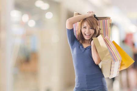 excitacion: Compras de la mujer alegre de celebraci�n de las bolsas asi�ticas. Foto de archivo
