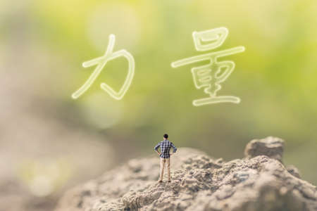 force of the nature: one person stand in the outdoor and looking up the Chinese text(mean power) on nature background, concept of power, strength, force. Stock Photo