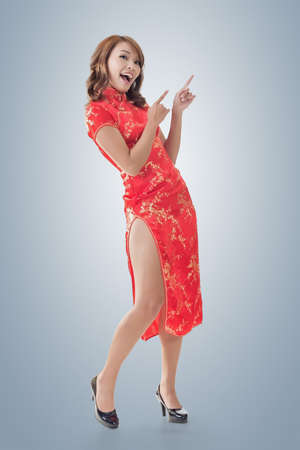 introducing: Chinese woman dress traditional cheongsam at New Year and introducing, full length portrait isolated.