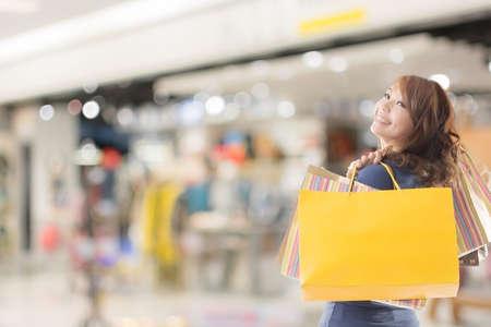Fröhlich Shopping-Frau des asiatischen mit Taschen.