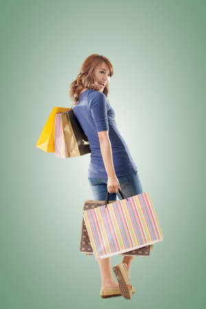 Cheerful shopping woman of Asian holding bags, full length portrait isolated. Stock Photo