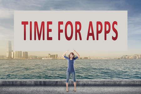simbolo de la mujer: Tiempo para las aplicaciones, las palabras en espera la tarjeta en blanco por una joven en el aire libre.