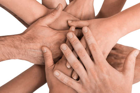 people working together: Group of hands holding together on white background. Stock Photo