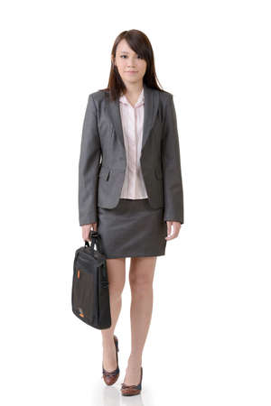 kindly: Walking business woman holding briefcase, full length portrait on white background.