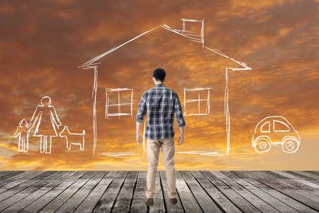 O homem asiático olha para a casa e a família do desenho no céu. Foto de archivo