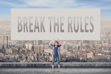 break the rules: Break the rules, words on blank board hold by a young girl in the outdoor. Stock Photo