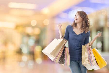 sorprendido: Compras de la mujer alegre de celebración de las bolsas asiáticas. Foto de archivo