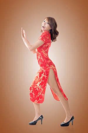 sexy asian girl: Chinese woman dress traditional cheongsam and push something at New Year, full length portrait isolated.