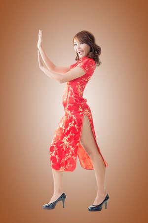 伝統: Chinese woman dress traditional cheongsam and push something at New Year, full length portrait isolated.