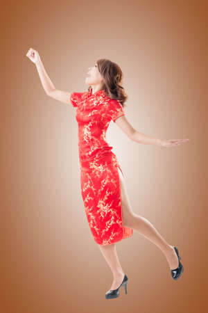 qipao: Smiling and excited Chinese woman dress traditional cheongsam at New Year, studio shot isolated.