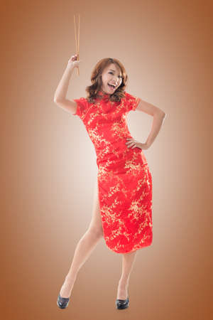 chipao: Smiling Chinese woman dress traditional cheongsam standing and holding chopsticks at New Year, full length portrait isolated. Stock Photo
