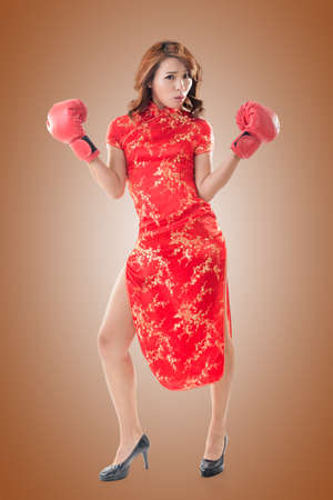 chipao: Chinese woman dress traditional cheongsam and boxing gloves, full length portrait isolated. Stock Photo