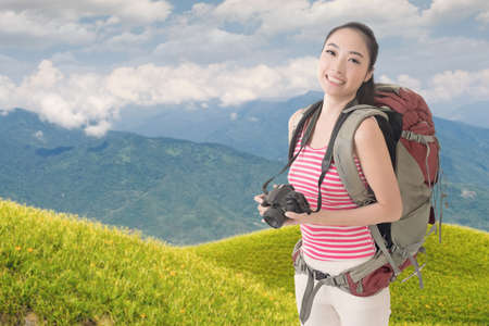 avocation: Happy smiling Asian young female backpacker with camera standing in front of tiger lily farm in Liushidan mountain, Fuli Township, Hualien County, Taiwan, Asia.